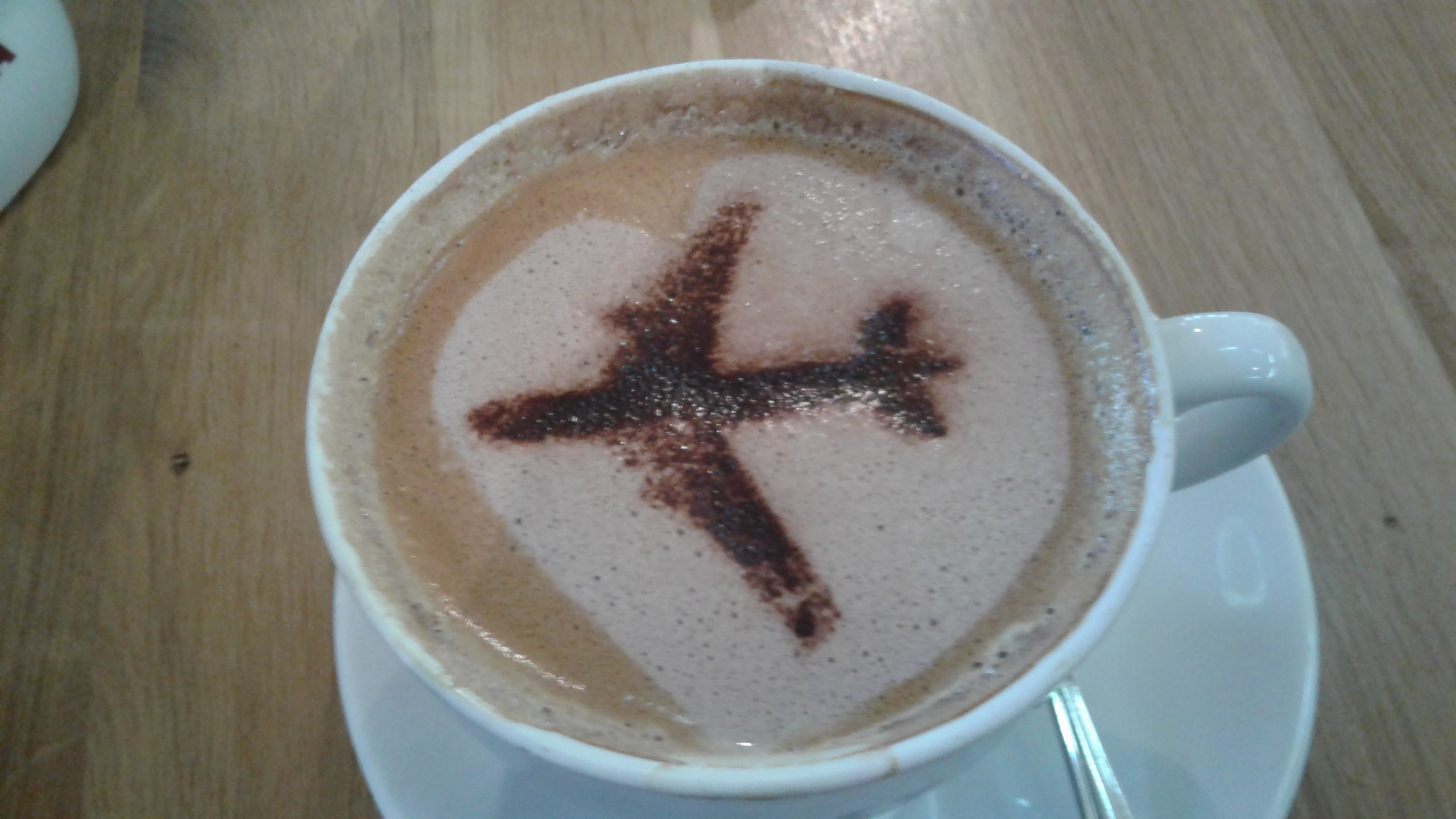 Coffee decorated with cocoa powder in the shape of an airplane