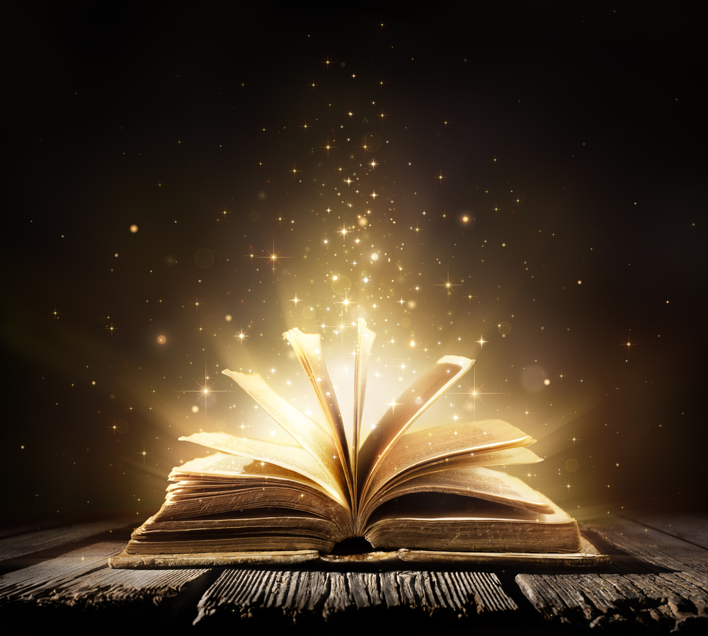 Book opening with magic gold lights coming from the pages